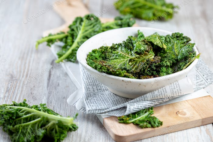 Homemade Green Kale Chips on vintage newspapper, white background
