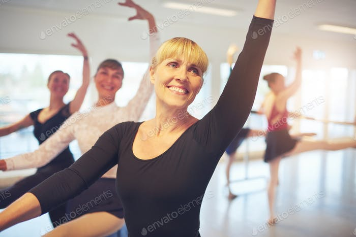 Smiling Mature ballet dancer exercising in ballet class