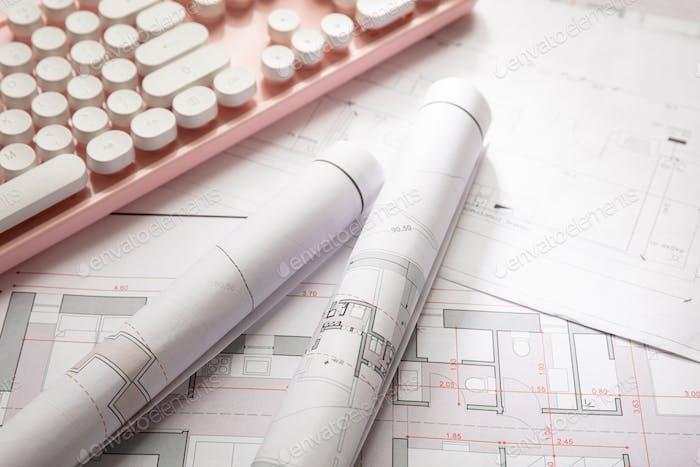 Baukonzept Wohngebäude Blaupause Zeichnungen und eine rosa Computertastatur