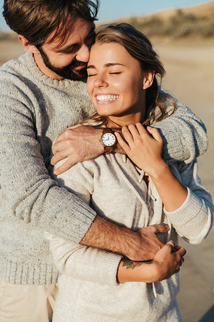 Loving couple outdoors at beach hugging.