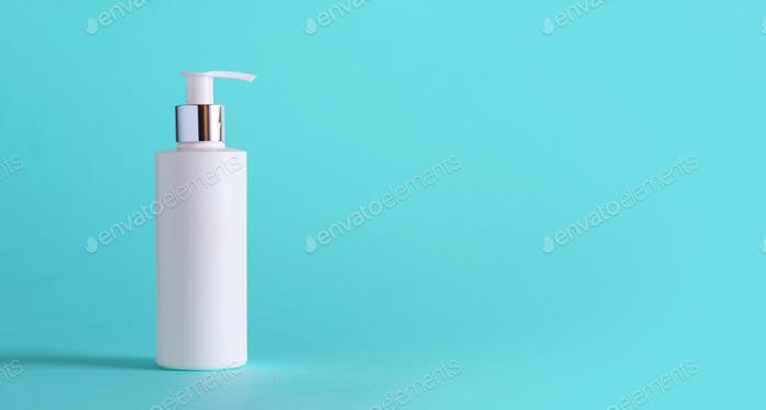 White bottle of moisturizing lotion on blue background with copy space. Minimalism style. Skin care
