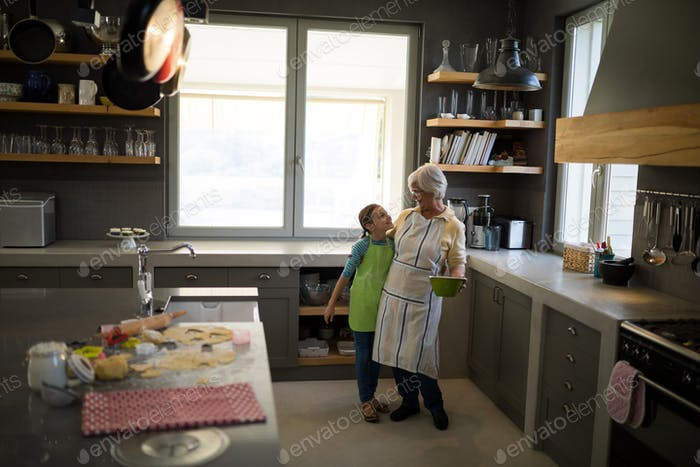 Grandmother and granddaughter embracing in the kitchen
