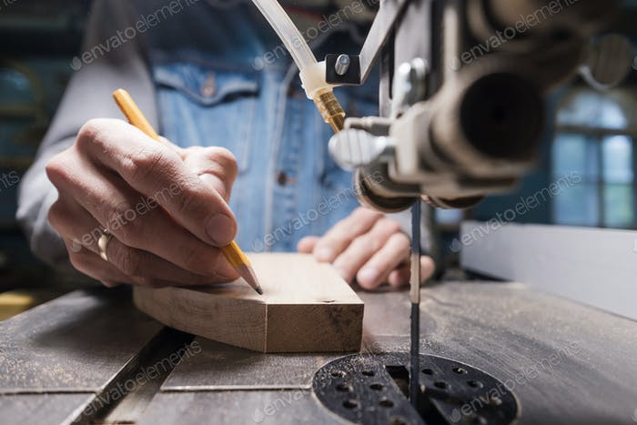View of a carpenter using a pencil to draw a line on a wooden plank.