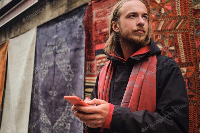 Hombre joven con estilo cuidadosamente mirando lejos de pie con un teléfono inteligente en el mercado local