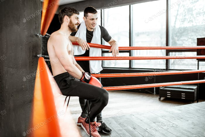 Boxing trainer with boxer on the boxing ring
