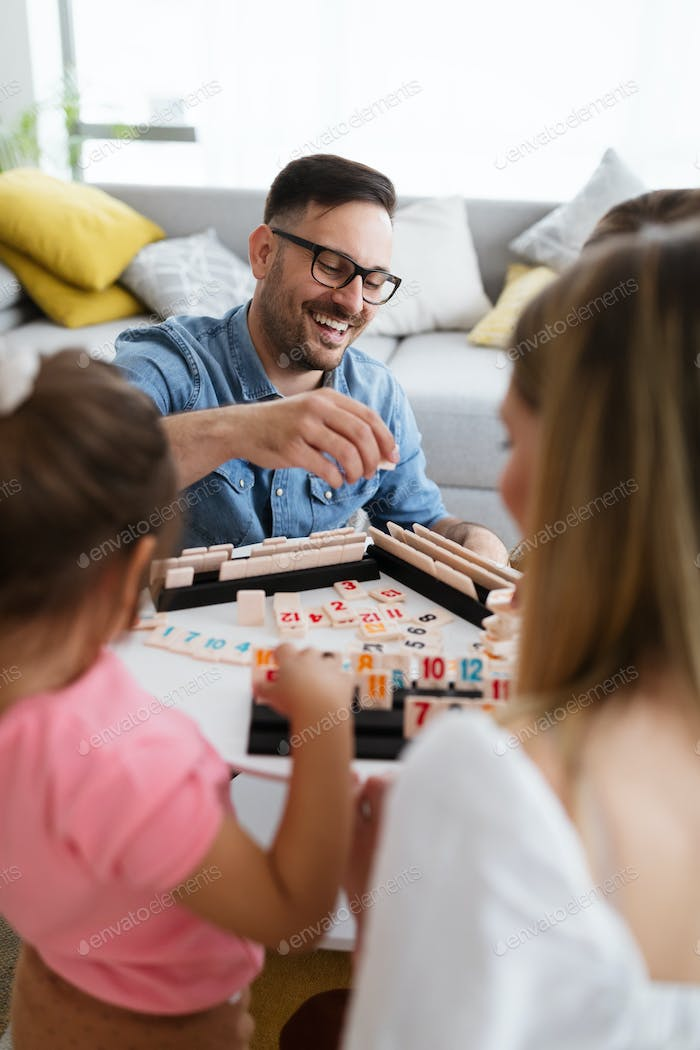 Happy young parents and children having fun, playing board game at home