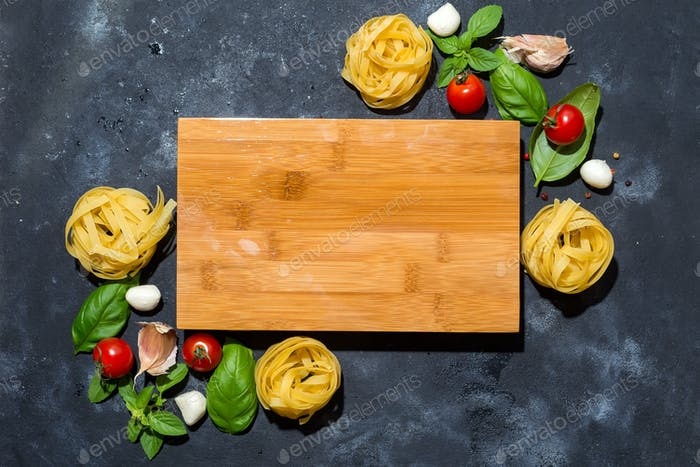 Italian fettuccine nests with tomatoes, olive oil and basil in the form of a frame
