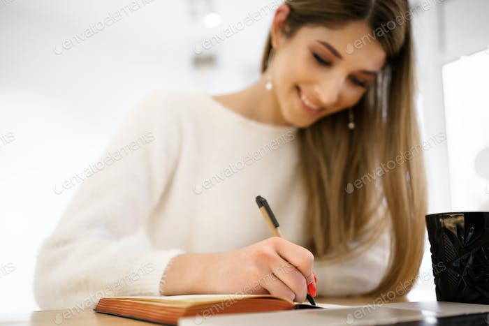 Smiling woman in white sweater writing in notebook