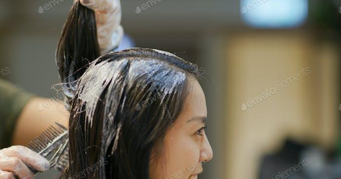 Woman dye her hair at beauty salon