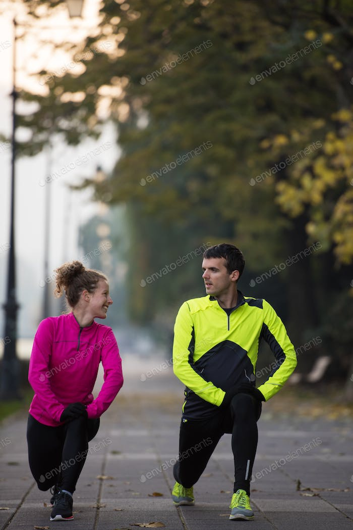 a young couple warming up before jogging