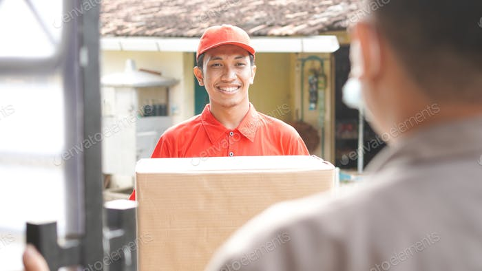 delivery man delivers the box to the customer and ok gesture