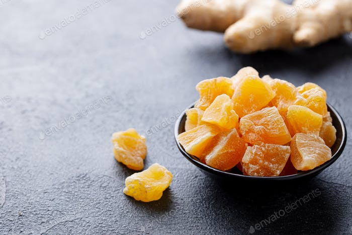 Candied Ginger in Black Bowl on Dark Stone Background. Close up. Copy Space.