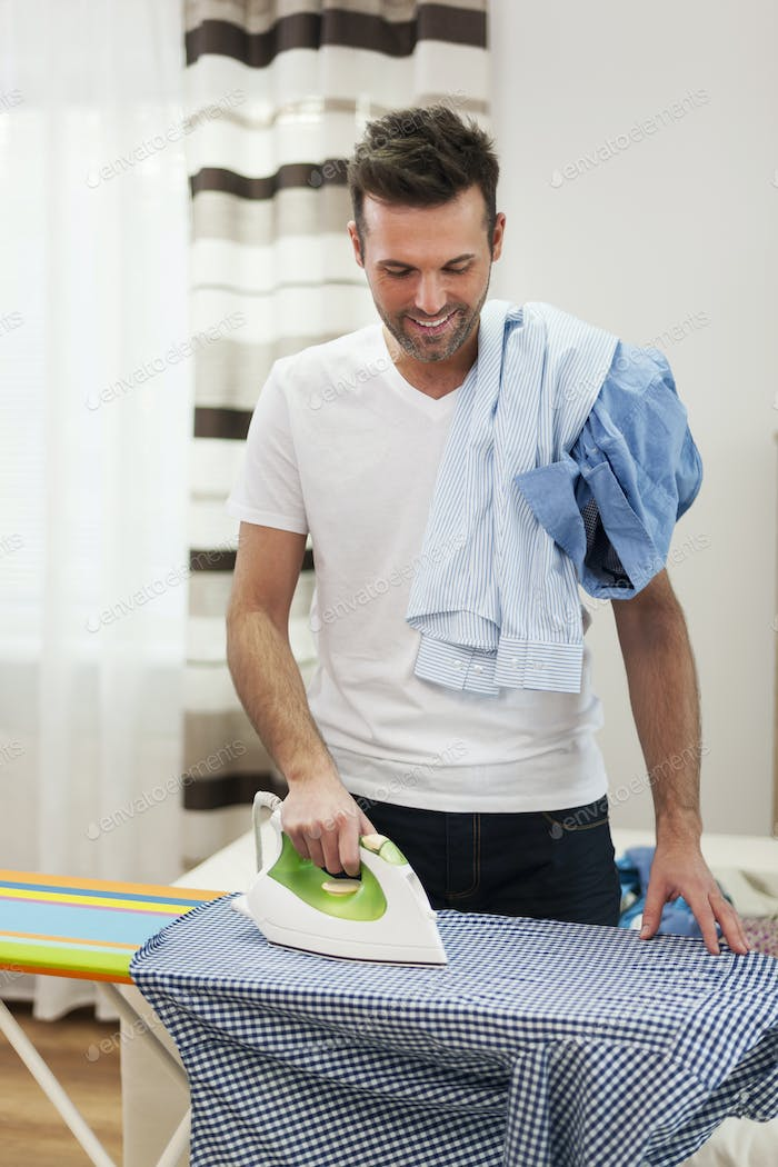 Smiling man ironing his shirts