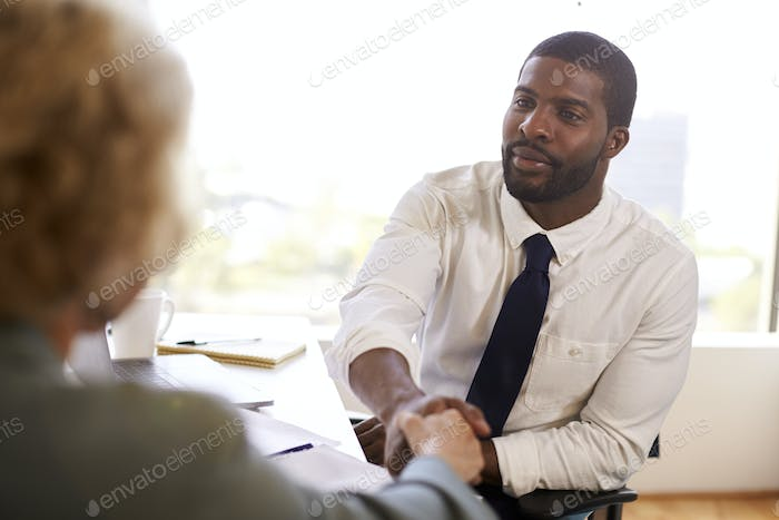 Senior Woman Shaking Hands With Male Doctor Financial Advisor Cosmetic Surgeon In Office