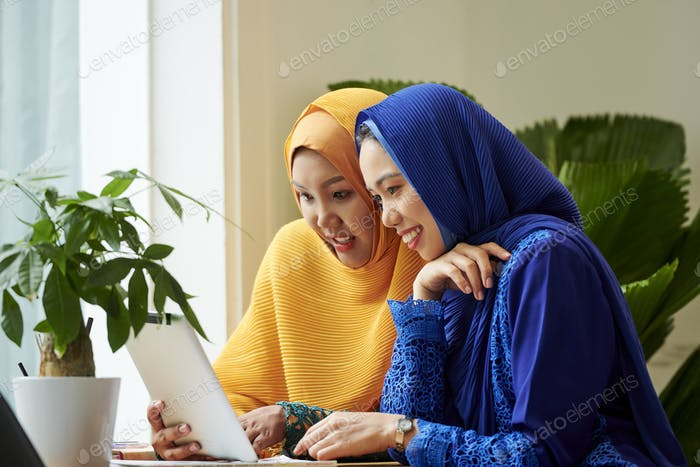 Female friends discussing information on tablet computer