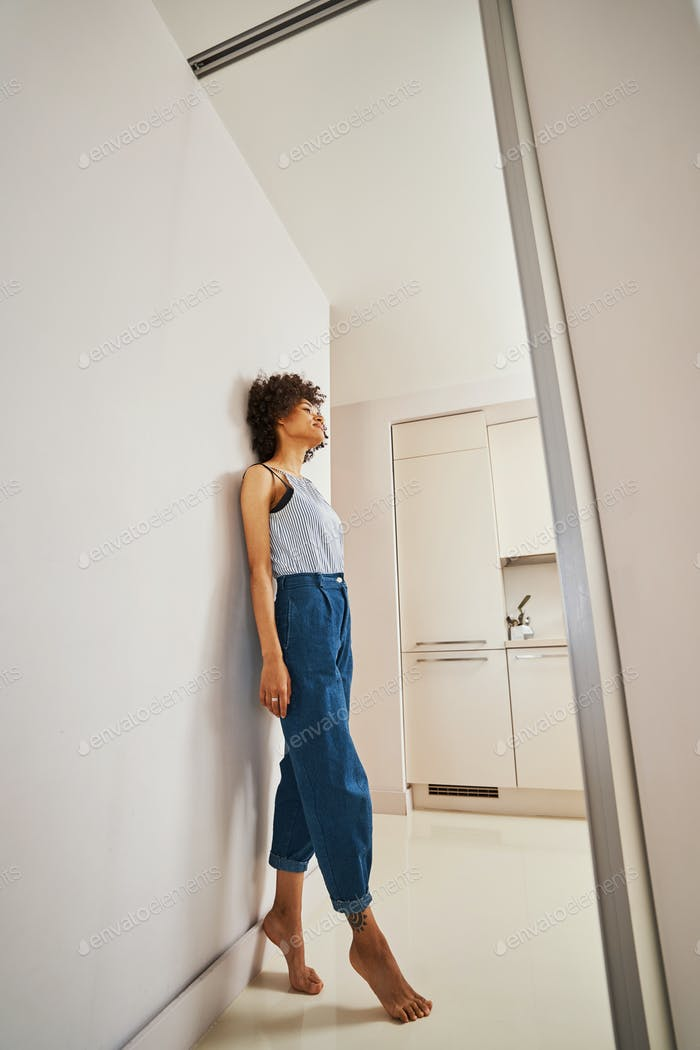 Barefoot woman daydreaming leaned back against the wall