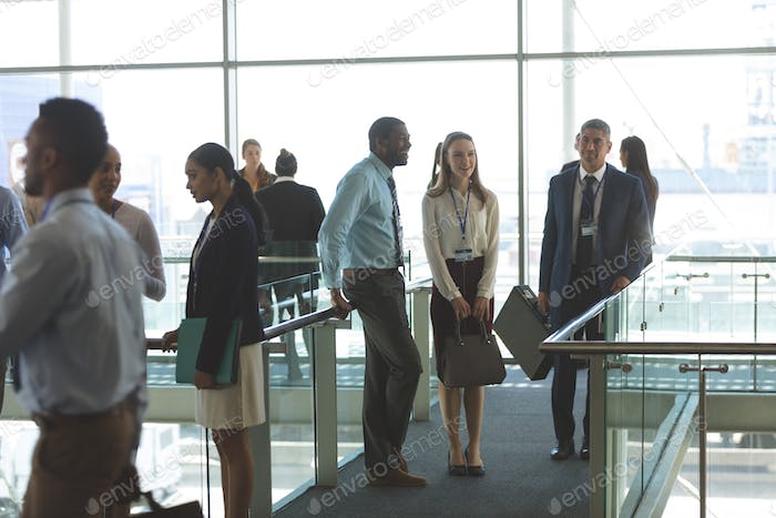 Front view of smiling diverse business executives interacting with each other in office lobby