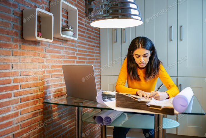 Female architect working at home with a laptop and blueprints