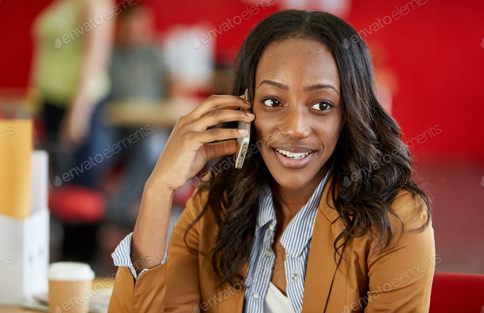 Confident female designer talking on a mobile phone in red creat