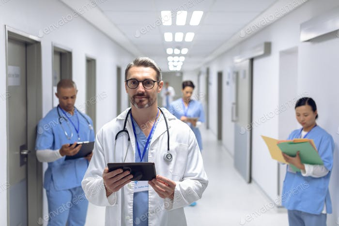 Caucasian male doctor standing with digital tablet in corridor at hospital.