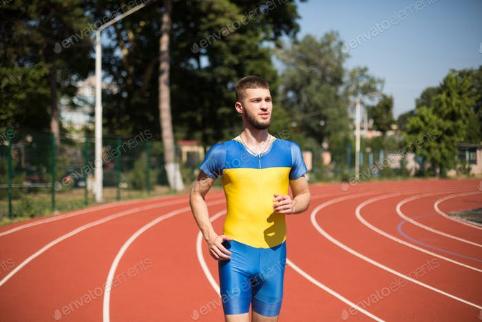 Young professional sportsman running on treadmill of stadium