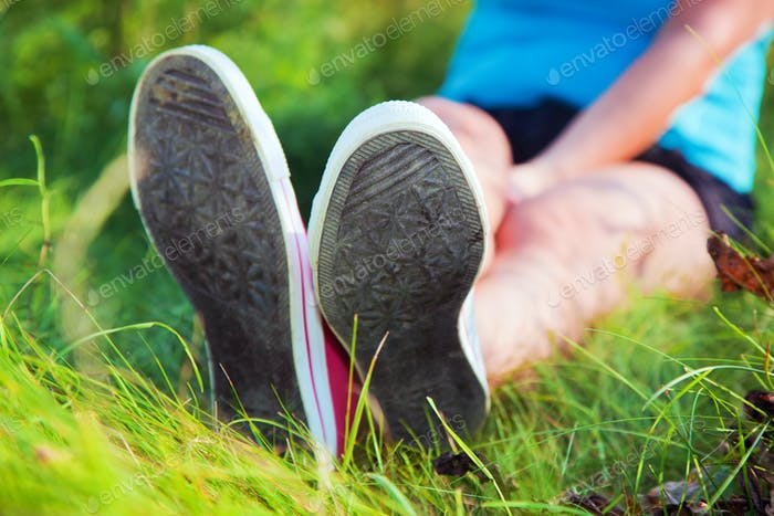 Pink sneakers on girl legs on grass