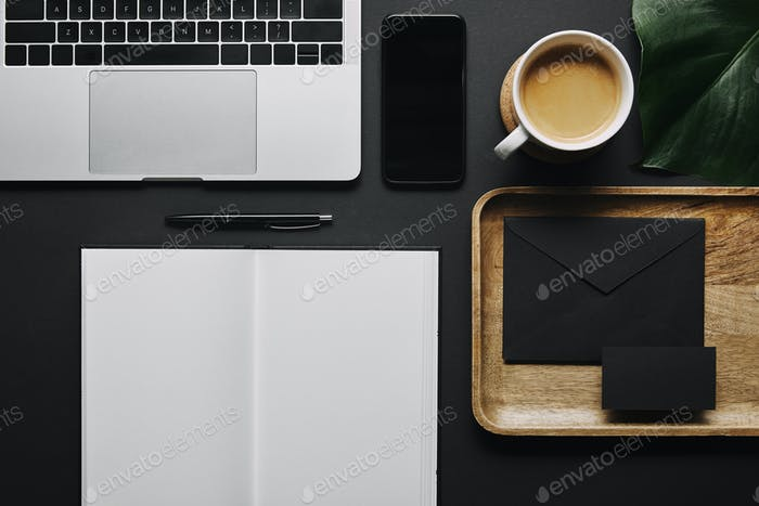 Open notebook and stationery by laptop on black background