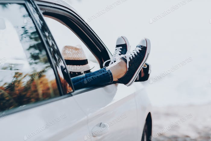Woman's legs in sneakers in the window car with straw hat.
