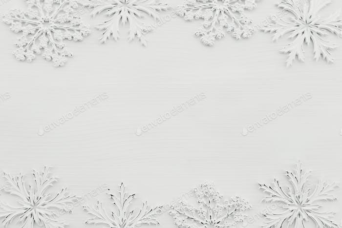 Wallpaper with white snowflakes on white wooden background