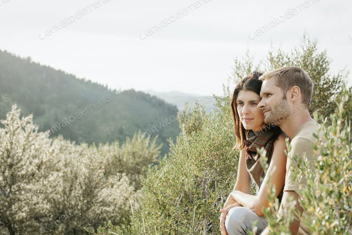 A couple in the mountains, sitting side by side looking at the view.
