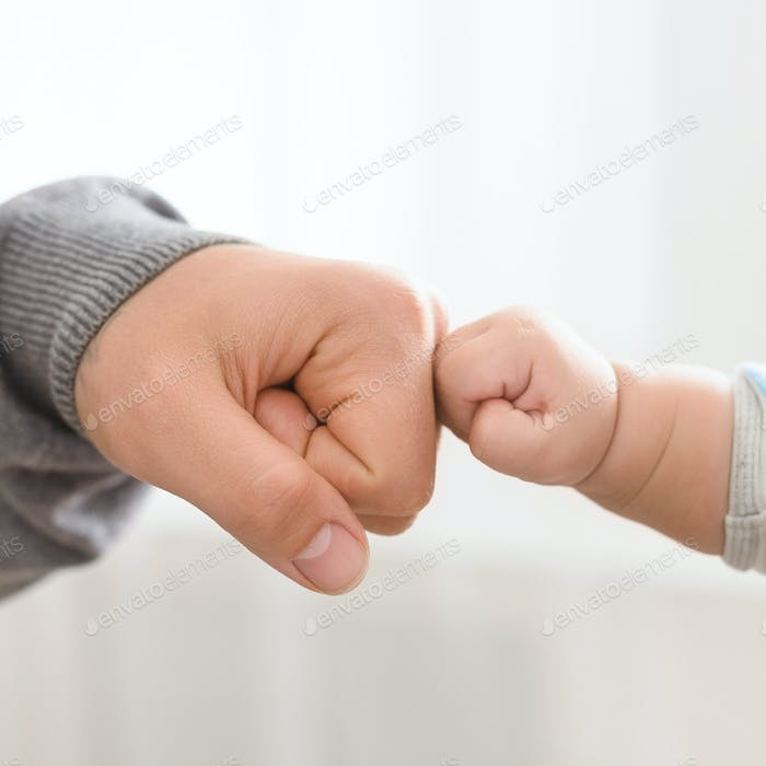 Close up of father holding baby hand
