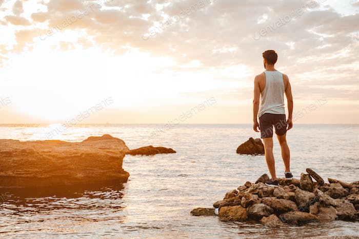 Young handsome man athlete standing at the rocky beach
