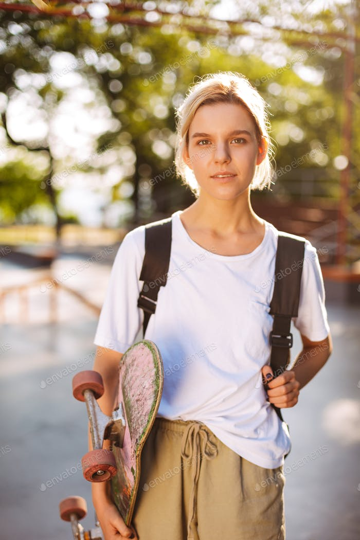 Beautiful girl with backpack and skateboard in hand dreamily loo