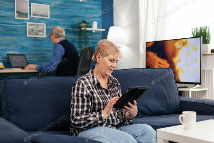 Happy mature woman relaxing on couch