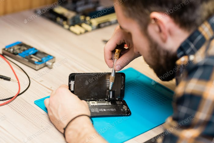 Professional gadget repair service master fixing tiny details with screwdriver