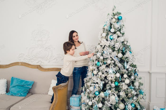 Portrait of happy boy with his mother decorating Christmas tree