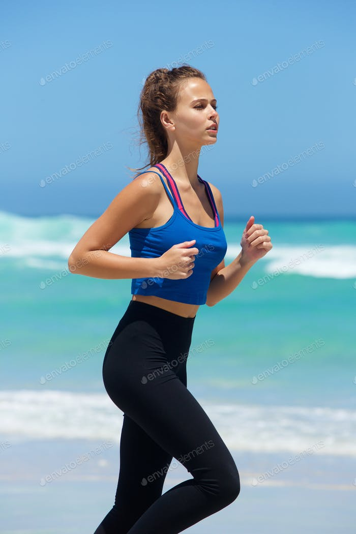 Active young woman running by the sea