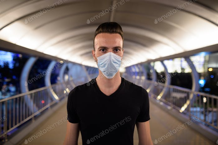 Man at night standing in city wearing face mask