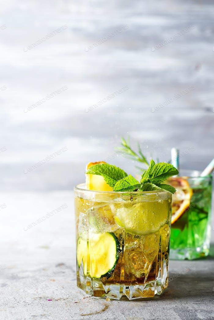 alkoholischer Sommer-Zitruscocktail mit Orangen-, Pfefferminz- und Gurkeneis in stiellosen Gläsern