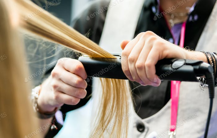 Professional hairdresser straightening long blond hair using straightener