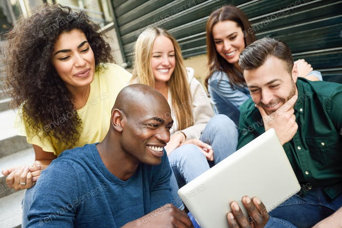 Multi-ethnic group of young people looking at a tablet computer
