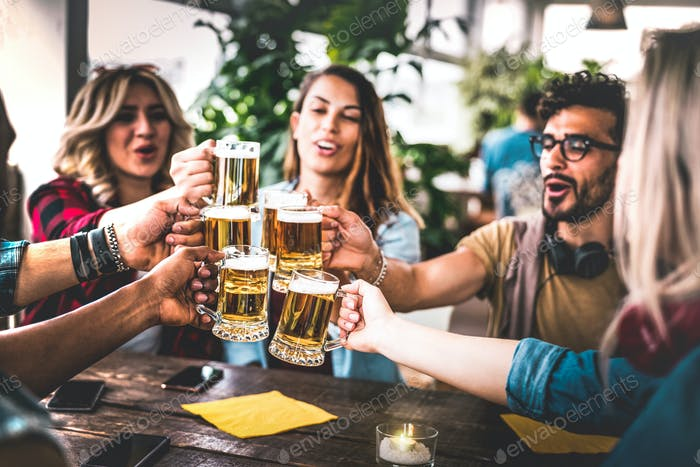 Friends toasting beer at brewery bar indoor at rooftop party