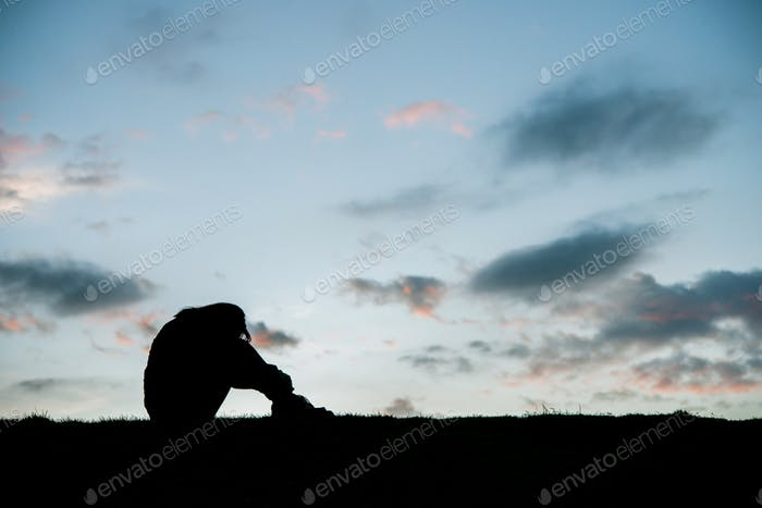 Silhouette of sad woman head on knees at sunset.