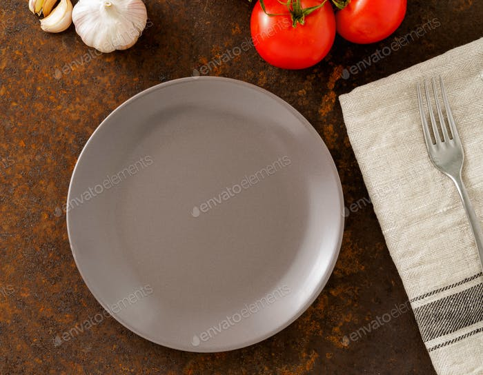 clean empty gray plate and fork on linen napkin on rusted old iron table