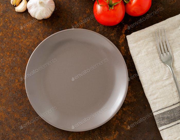 saubere leere graue Platte und Gabel auf Leinenserviette auf verrosteten alten Eisentisch