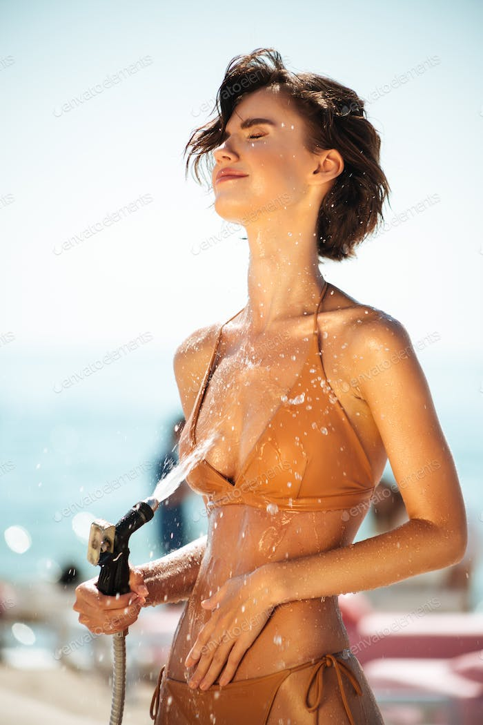 Young girl dreamily closing her eyes while pouring water from hose on beach