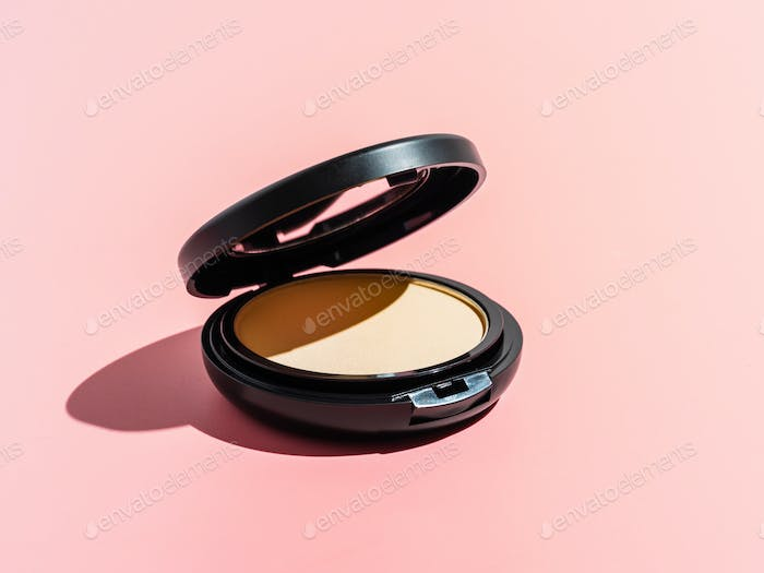Compact powder on pink background, copy space