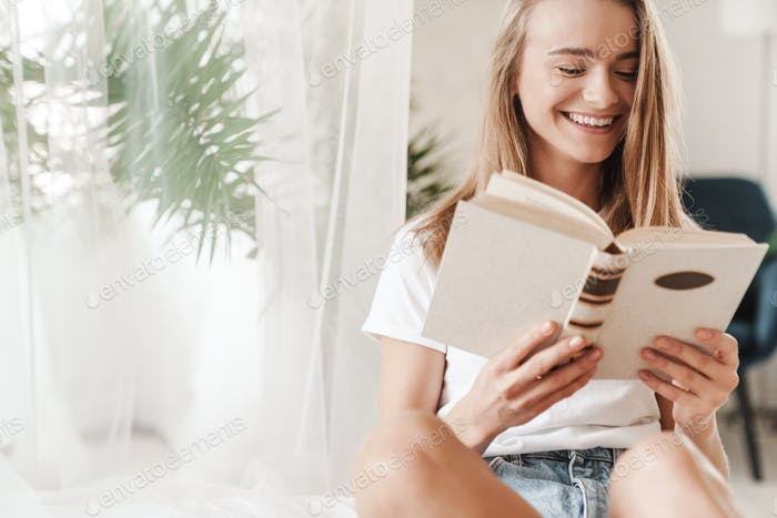 Image of laughing young woman reading book while sitting on bed