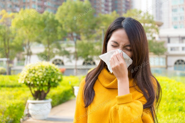 Asian Young Woman got allergy of nose when standing outdoor