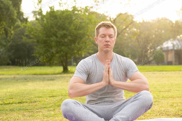 Young handsome man with eyes closed meditating at the park